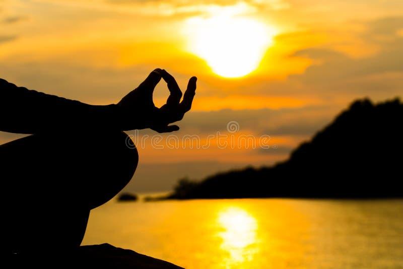 Silhouet, hand die van Vrouw in Yoga het mediteren stelt of Lotus Posit stock foto's