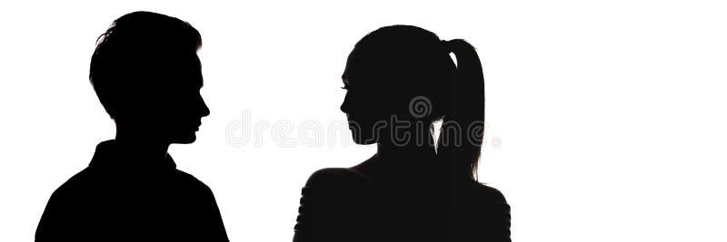 Silhouet hoofdprofiel van kerel en een meisje die elkaar, gezichten van ernstige tieners, vergelijking bekijken van geslachten, stock afbeelding