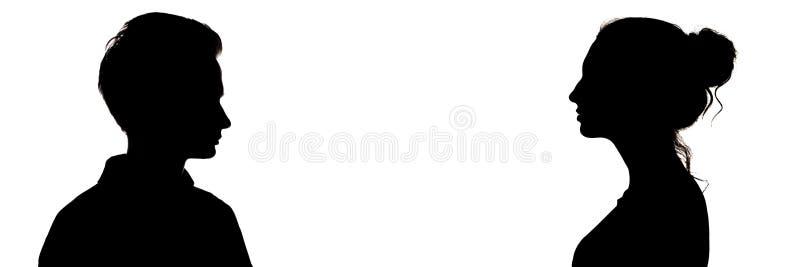 Silhouet hoofdprofiel van kerel en een meisje die elkaar, gezichten van ernstige tieners, vergelijking bekijken van geslachten, stock fotografie