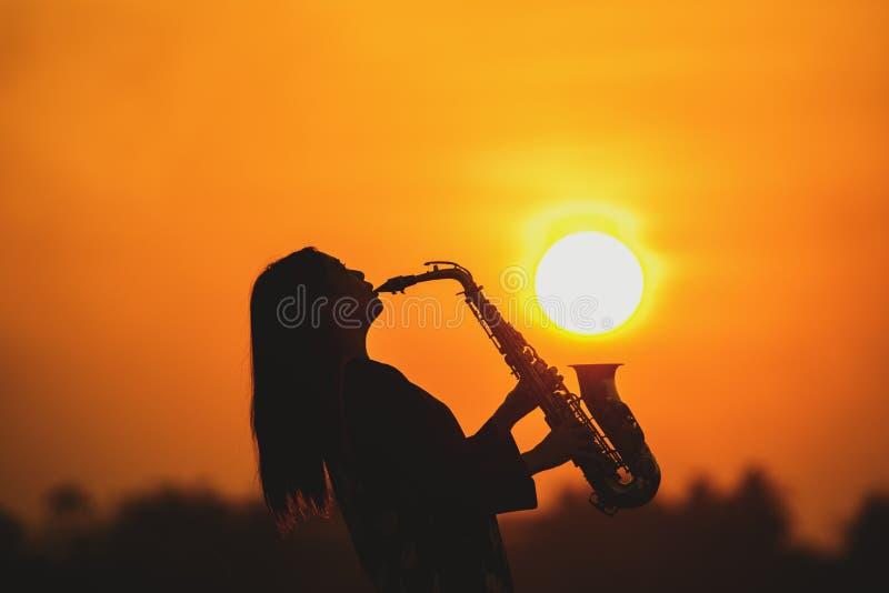 Silhouet jonge vrouw die de saxofoon spelen royalty-vrije stock fotografie
