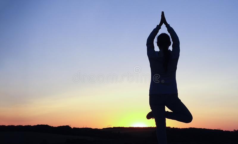 Silhouet jonge vrouw het praktizeren yoga en Meditatie bij zonsondergang stock foto