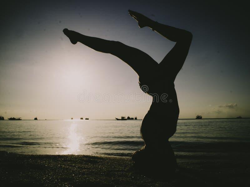 Silhouet jonge vrouw het praktizeren yoga op het strand bij zonsondergang royalty-vrije stock foto