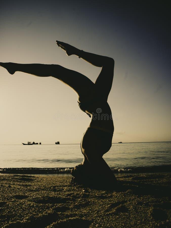 Silhouet jonge vrouw het praktizeren yoga op het strand bij zonsondergang stock foto's