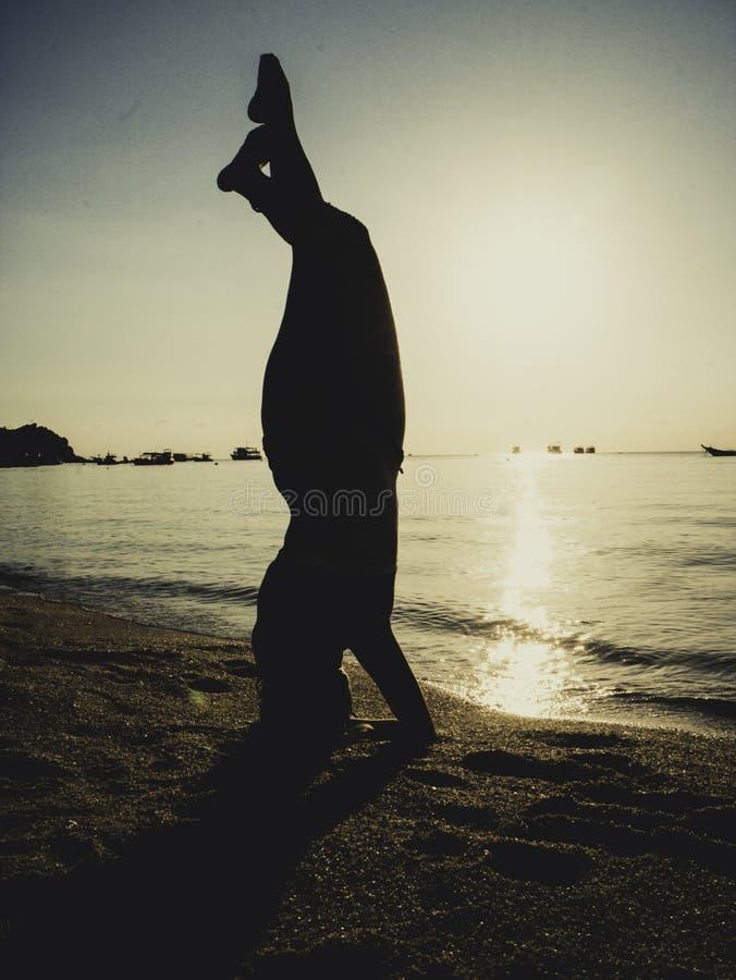 Silhouet jonge vrouw het praktizeren yoga op het strand bij zonsondergang royalty-vrije stock afbeelding