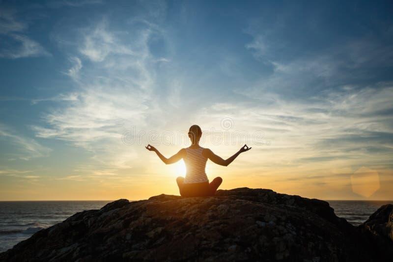 Silhouet jonge vrouw het praktizeren yoga op het zonsondergangstrand royalty-vrije stock foto's