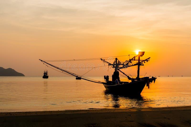Silhouet Kleine vissersboten op het overzees tijdens zonsopgang stock foto's