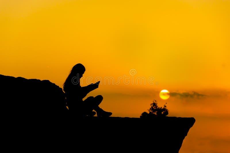 Silhouet, meisje die een boek lezen bij zonsondergang stock foto