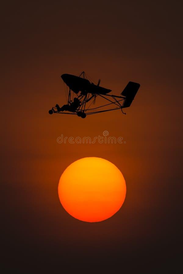 Silhouet microlight vliegtuigen met zonsondergangachtergrond stock afbeeldingen