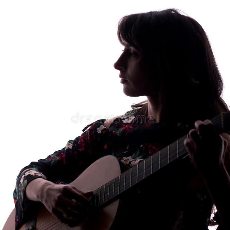 Silhouet Mooi meisje met een gitaar op een witte achtergrond De ruimte van het exemplaar Een vierkant beeld royalty-vrije stock foto