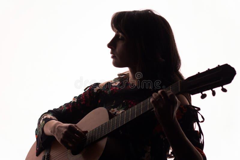 Silhouet Mooie meisjesspelen op een akoestische gitaar op een witte achtergrond De ruimte van het exemplaar stock foto's