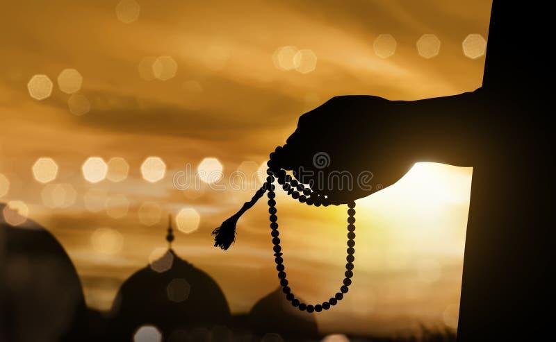 Silhouet moslimmens die met gebedparels bidden stock afbeelding