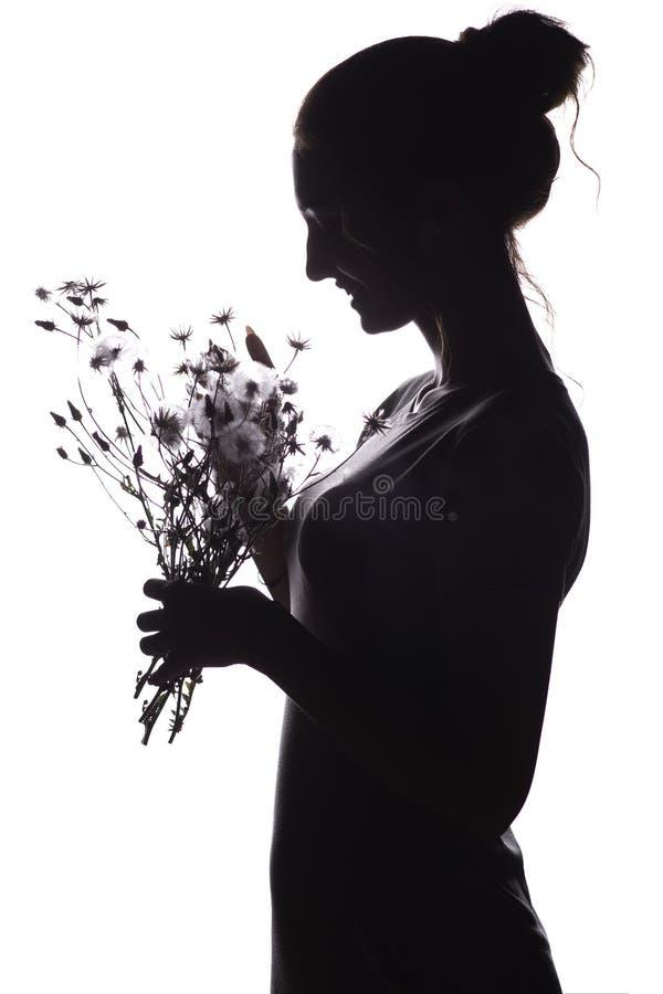 Silhouet pof een mooi meisje met een boeket van droge paardebloemen, het gezichtsprofiel van een dromerige jonge vrouw op een geï royalty-vrije stock foto's