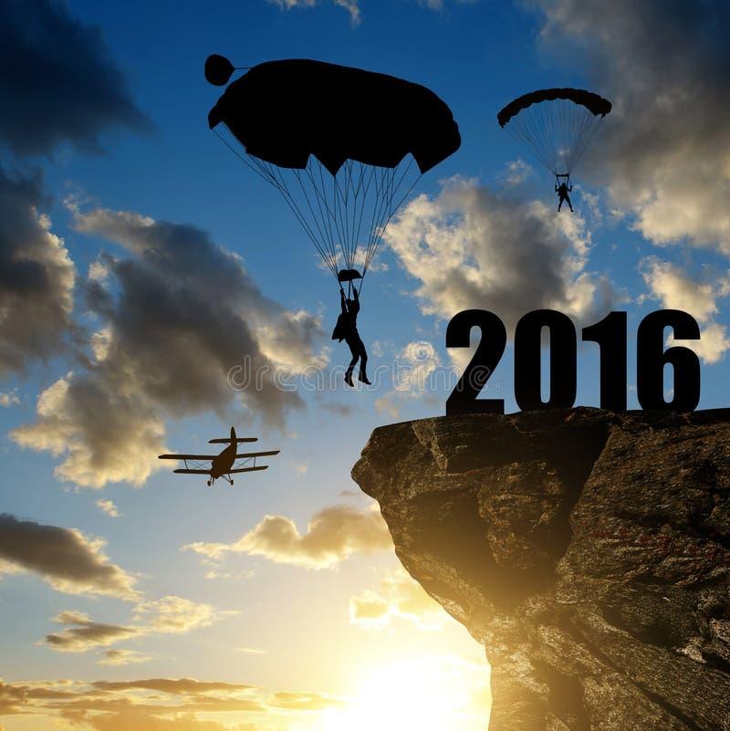 Silhouet skydiver parachutist die binnen aan het Nieuwjaar 2016 landen stock afbeeldingen