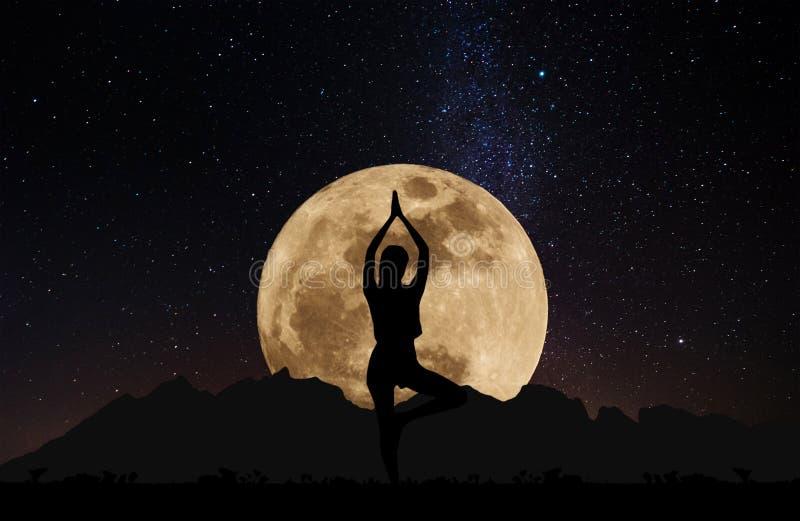 Silhouet stelt de jonge vrouw het praktizeren yoga bij nacht onder volle maan met hemelhoogtepunt van sterren royalty-vrije stock afbeelding