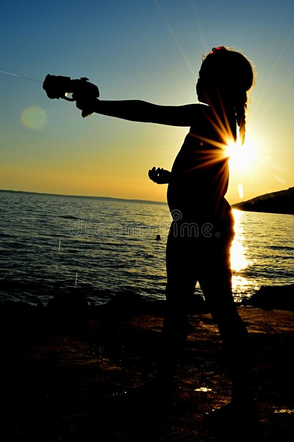 Silhouet te of little girl shooting with futuristic cyberpunk water pistol raised in left hand onrocky shore of Croatia. Silhouette of little girl shooting stock image