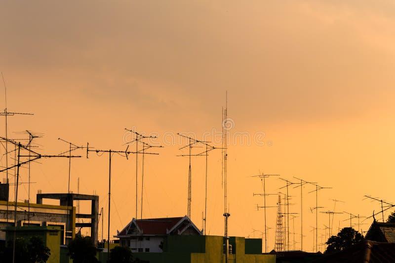 Silhouet, telecommunicatietorens met TV-antennes en satellietschotel in zonsondergang Vele opgezette antennes en satelliet van hu stock foto's