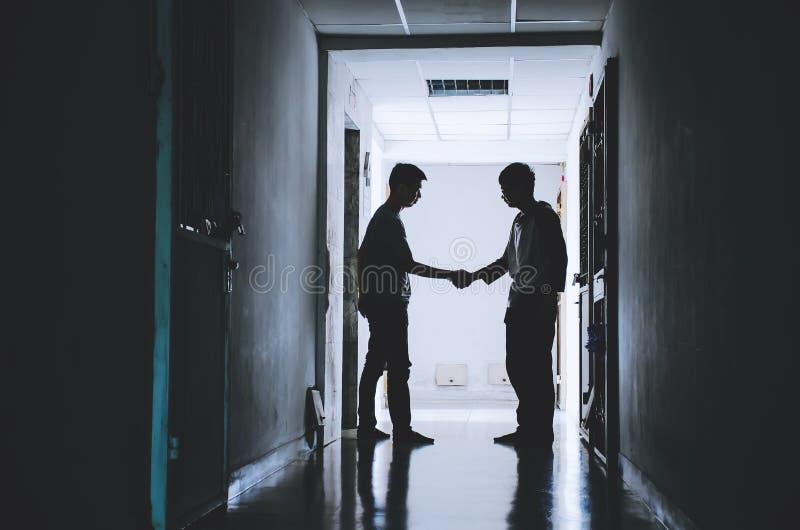 Silhouet twee de handen die van de vriendenschok een overeenkomst tussen van de gelukkige en succesvriendschap beëindigen stock foto's