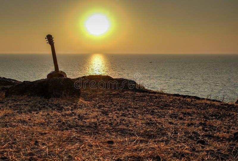 Silhouet van akoestische gitaar bij zonsondergang, Gokarna, India stock foto