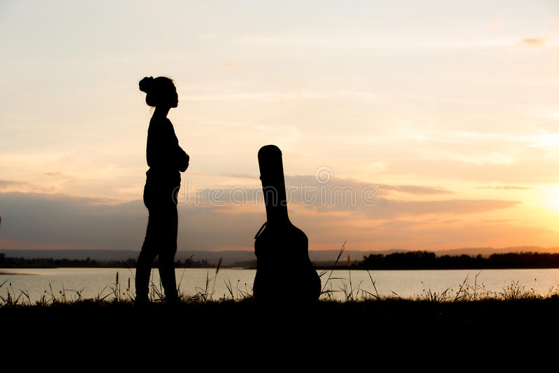Silhouet van Aziatisch meisje met gitaargeval stock afbeelding