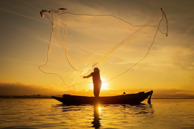 Silhouet van Aziatische visser op houten boot, visser in actie die een net voor het vangen van zoetwatervissen in aardrivier werp stock foto