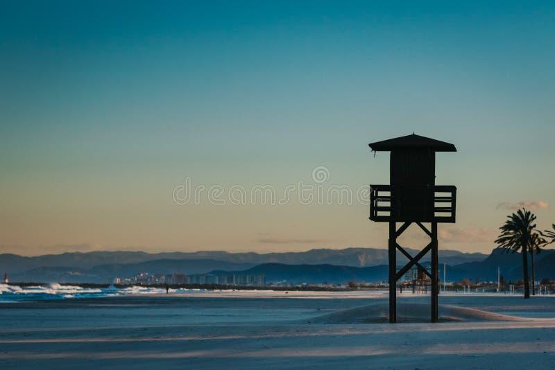 Silhouet van badmeestertoren in het beroemde strand van de de vakantiebestemming van Spanje Bergen en stad op de achtergrond met  royalty-vrije stock fotografie
