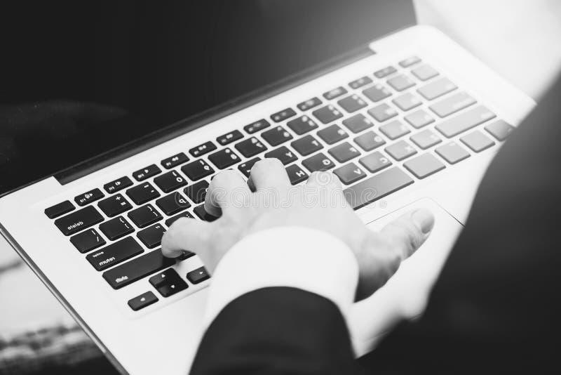 Silhouet van bebouwd schot van een jonge bedrijfsmens die aan notitieboekjecomputer op het zijn werk werken die technologie, gloe stock afbeelding