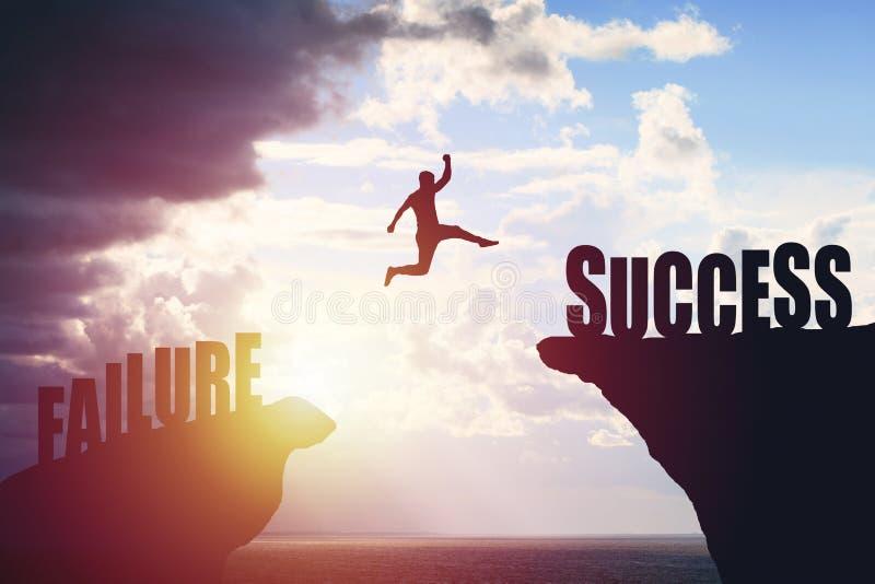Silhouet van bedrijfsmensensprong aan succestekst over een mooie achtergrond van de meningsberg royalty-vrije stock afbeeldingen