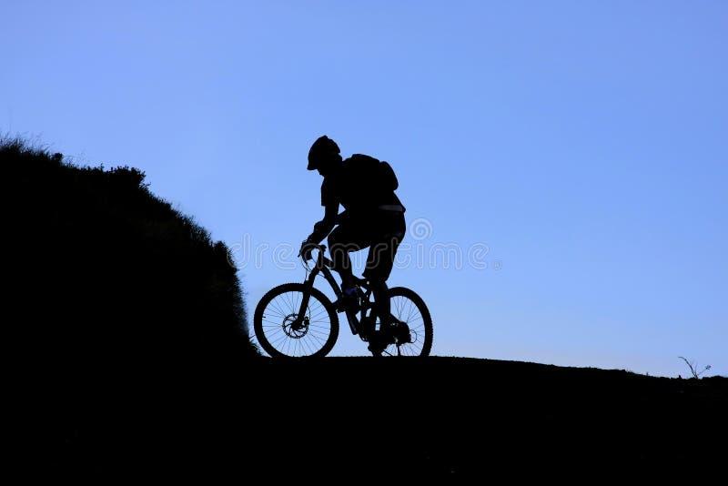 Silhouet van bergfietser stock afbeeldingen