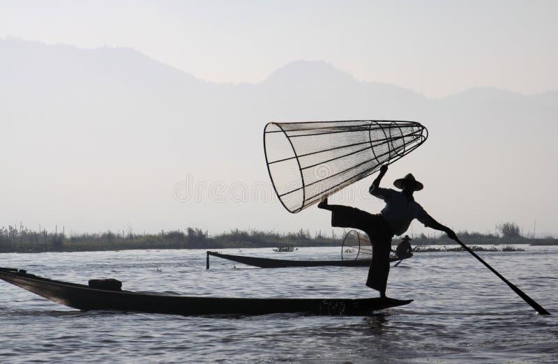 Silhouet van bergketen en het traditionele Birmaanse visser in evenwicht brengen op zijn boot in de dageraad op Inle-Meer, Myanma royalty-vrije stock afbeelding