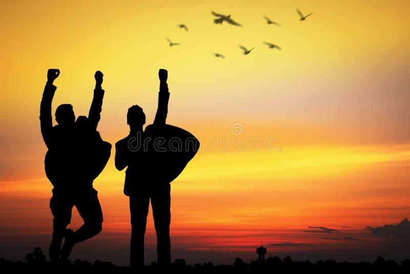 silhouet van bevrijd bedrijfsmensen die gelukkig voor succes springen, royalty-vrije stock afbeeldingen