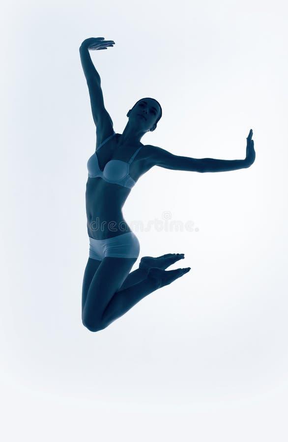 Silhouet van blauwe springende balletdanser stock foto's