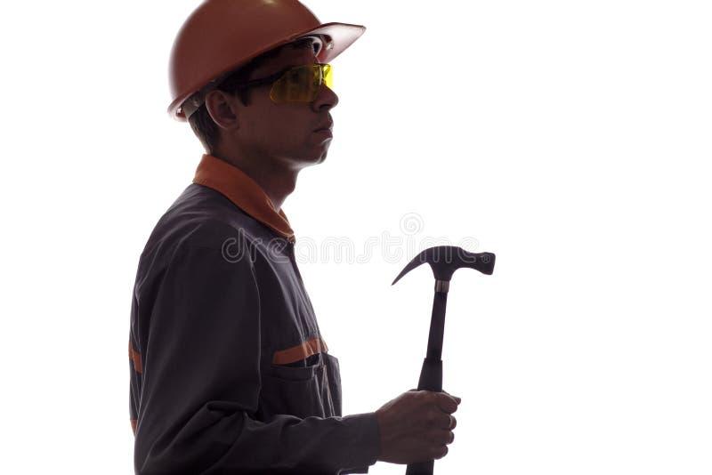 Silhouet van bouwvakker met hamer, de mens in bouwvakker en beschermende brillen in bouwrobe op wit geïsoleerde achtergrond royalty-vrije stock afbeeldingen