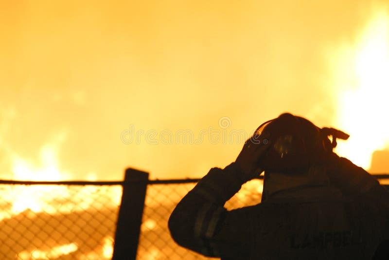 Silhouet van brandbestrijder bij een uitbarsting stock foto