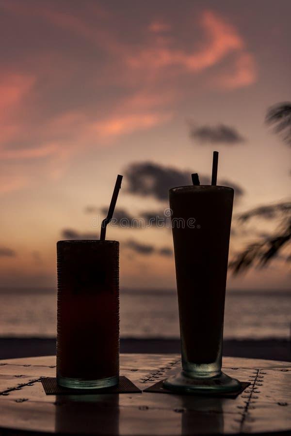 Silhouet van cocktail twee tijdens zonsondergang in een tropisch eiland Gelukkig Uur stock foto