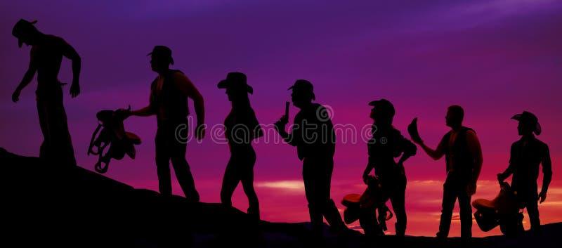 Silhouet van cowboys en veedrijfsters die in een lijn in de zonnen lopen stock foto