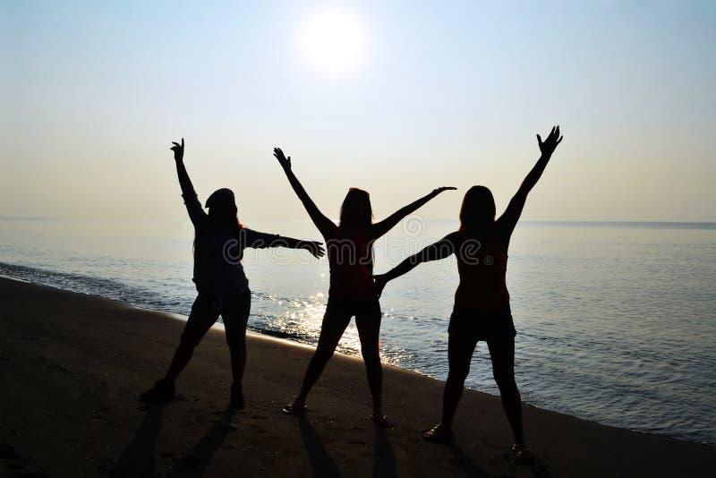 Silhouet van 3 dames met zonsopgang op het strand stock foto