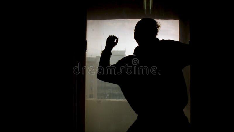 Silhouet van dander voor venster lengte Schaduw van de professionele danser van de mensenpool op pyloon dichtbij venster stock fotografie
