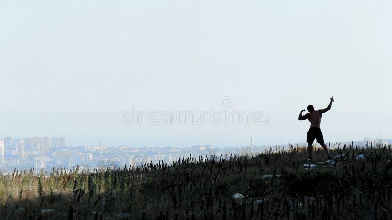 Silhouet van de Afrikaanse Amerikaanse atletische mens met het naakte torso stellen op de rots royalty-vrije stock afbeelding
