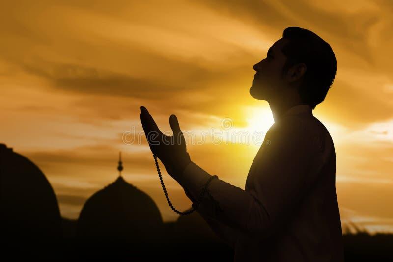 Silhouet van de Aziatische moslimmens die hand en het bidden opheffen stock afbeelding