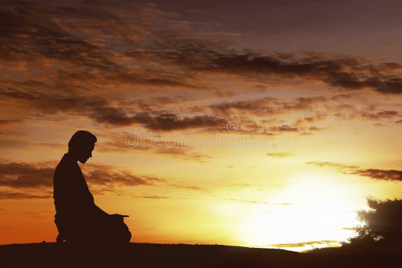 Silhouet van de Aziatische moslimmens die op een heuveltop bidden stock afbeeldingen