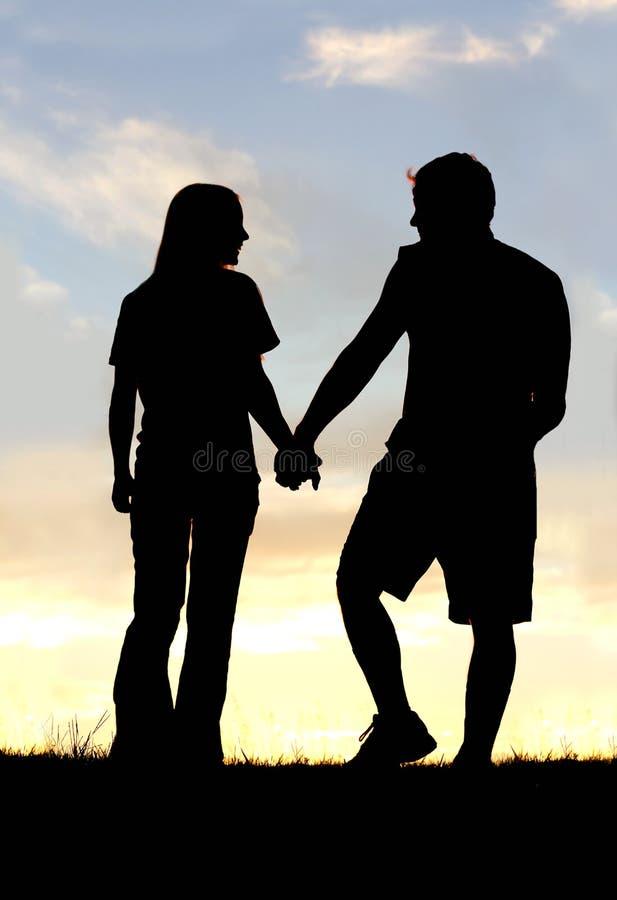 Silhouet van de Gelukkige Handen van de Paarholding op Gang bij Zonsondergang stock foto