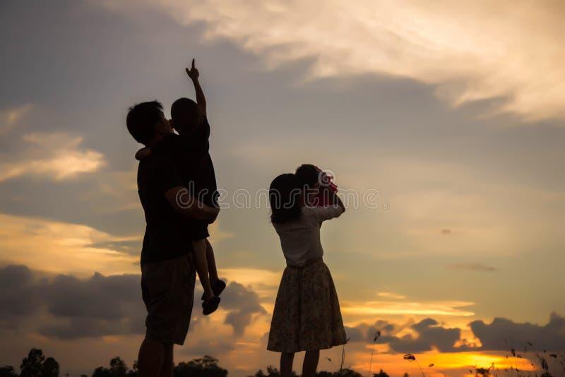 Silhouet van de gelukkige moeder en de zoon die van de familievader in openlucht spelen stock fotografie
