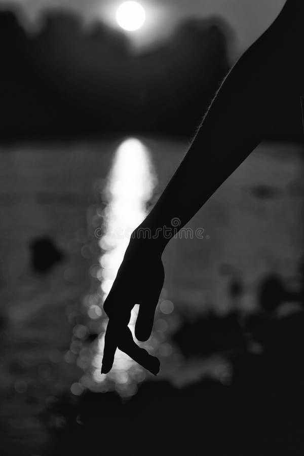 Silhouet van de hand Vrouwelijke hand op mooie zonsondergang royalty-vrije stock afbeeldingen