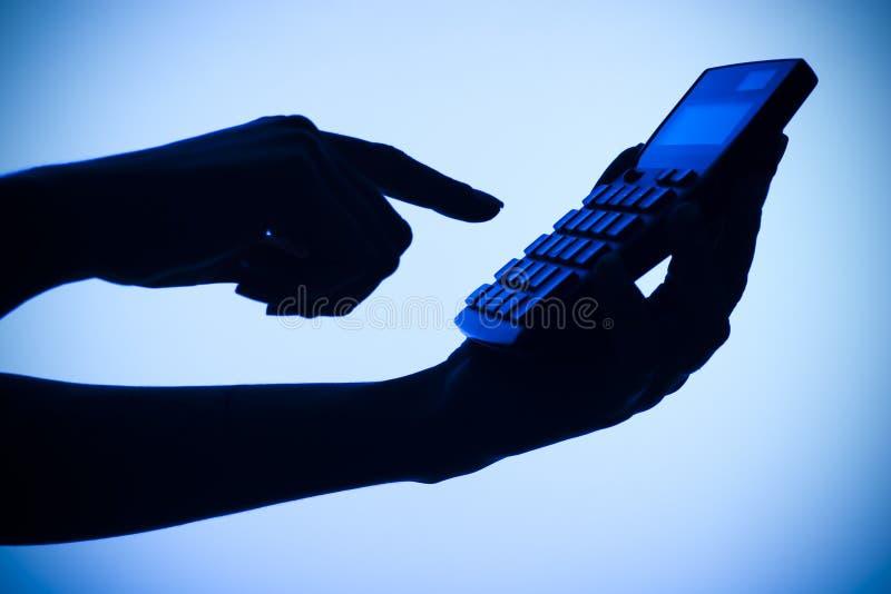 Silhouet van de handen van de vrouw met calculator stock afbeeldingen