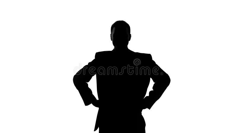 Silhouet van de handen van de zakenmanholding op zijn heup, ernst van bedoelingen stock fotografie