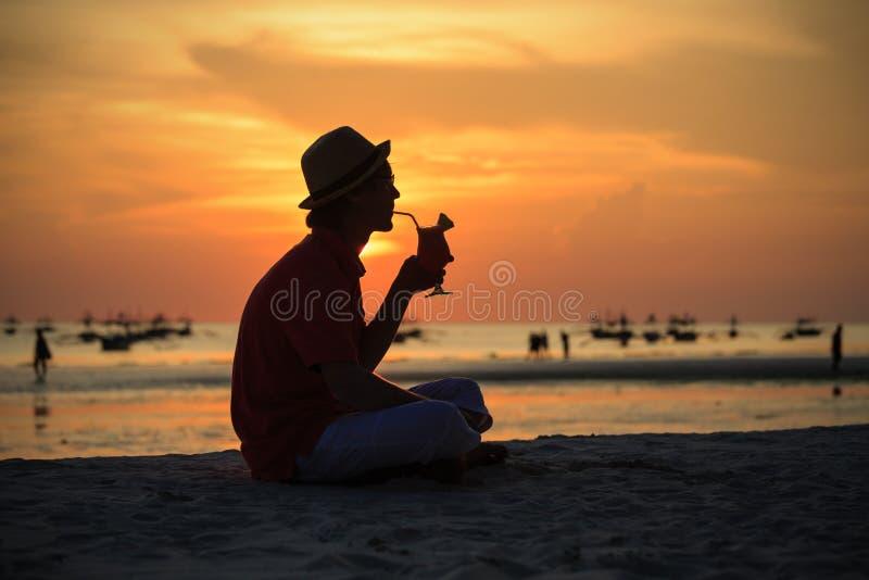Silhouet van de jonge mens die drank hebben bij zonsondergang royalty-vrije stock foto's