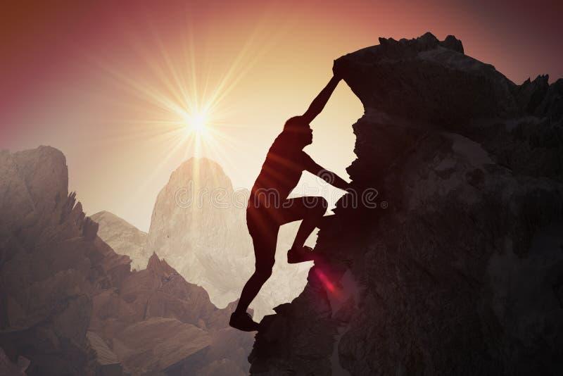 Silhouet van de jonge mens die op berg beklimmen stock fotografie