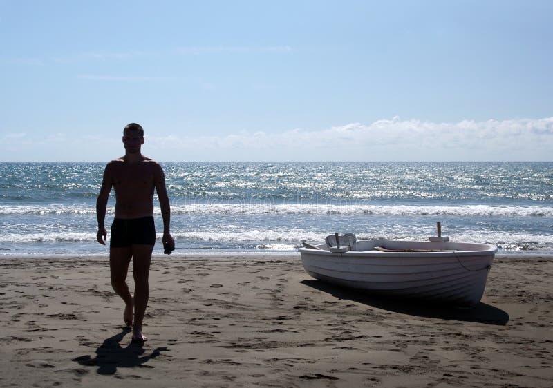 Silhouet van de jonge mens die op een strand loopt stock foto's