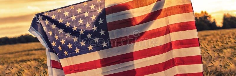 Silhouet van de Jonge Vlag van de V.S. van de Vrouwenholding op Gebied bij Zonsondergang royalty-vrije stock afbeelding