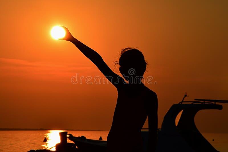 Silhouet van de kleine zon van de meisjesholding tijdens zonsondergang boven jachthaven, deel van motorboot een zichtbaar op rech stock foto